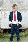 Boy in blue blazer with red tie on the farm