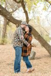 Couple cuddling under a tree in fall family photography session