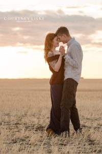 Couple dancing in a Saskatchewan field at sunset