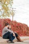Couple sitting in front of bush with fire red leaves