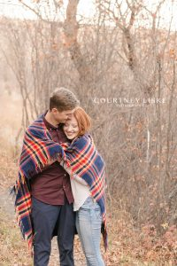 Couple snuggling under a blue and red plaid blanket