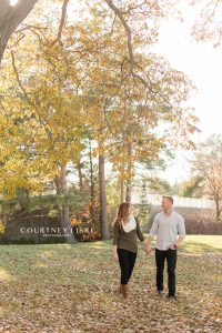 Engaged couple walking through the leaves at the University of Regina