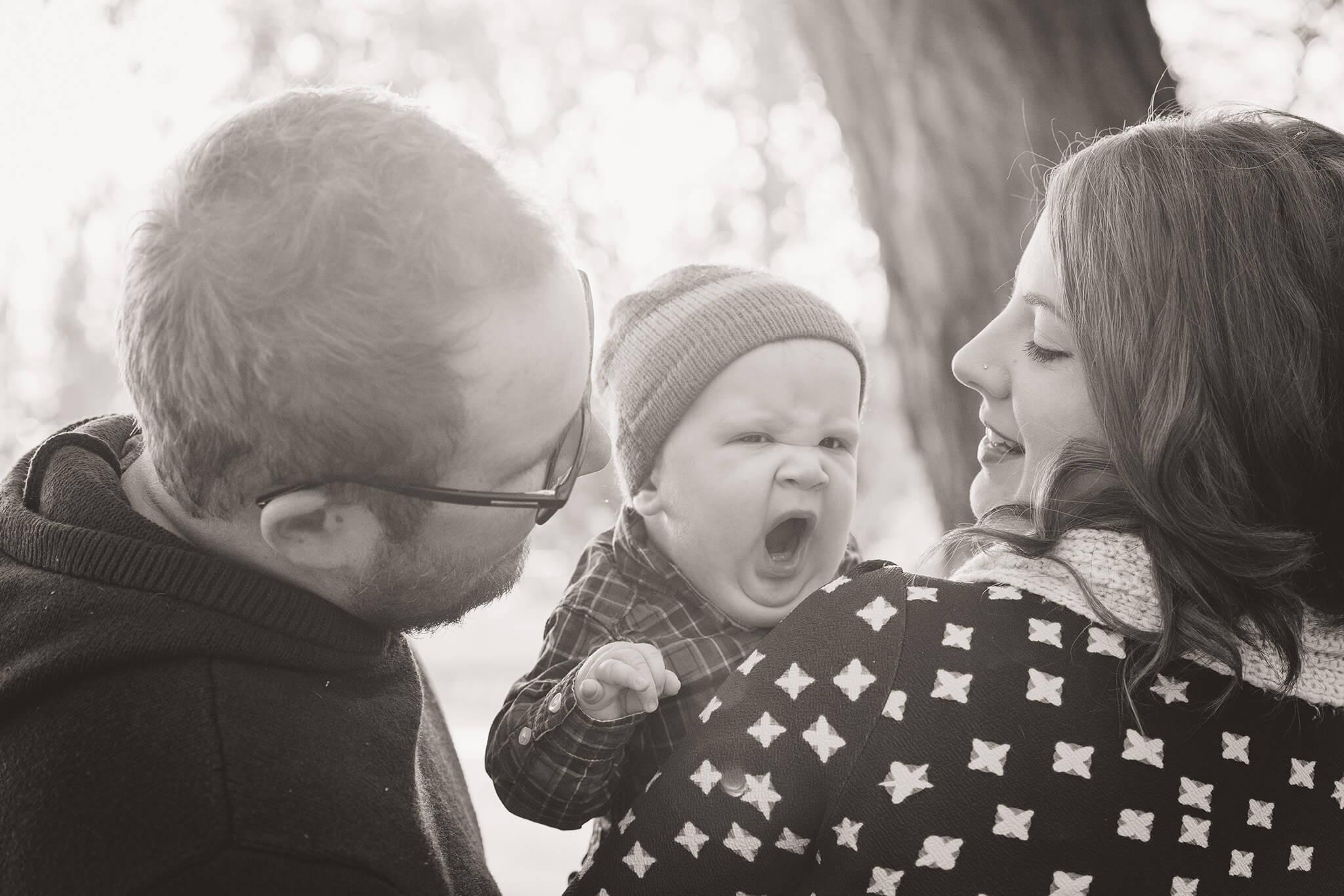 Little boy yawns with mom and dad on a walk in Regina Saskatchewan