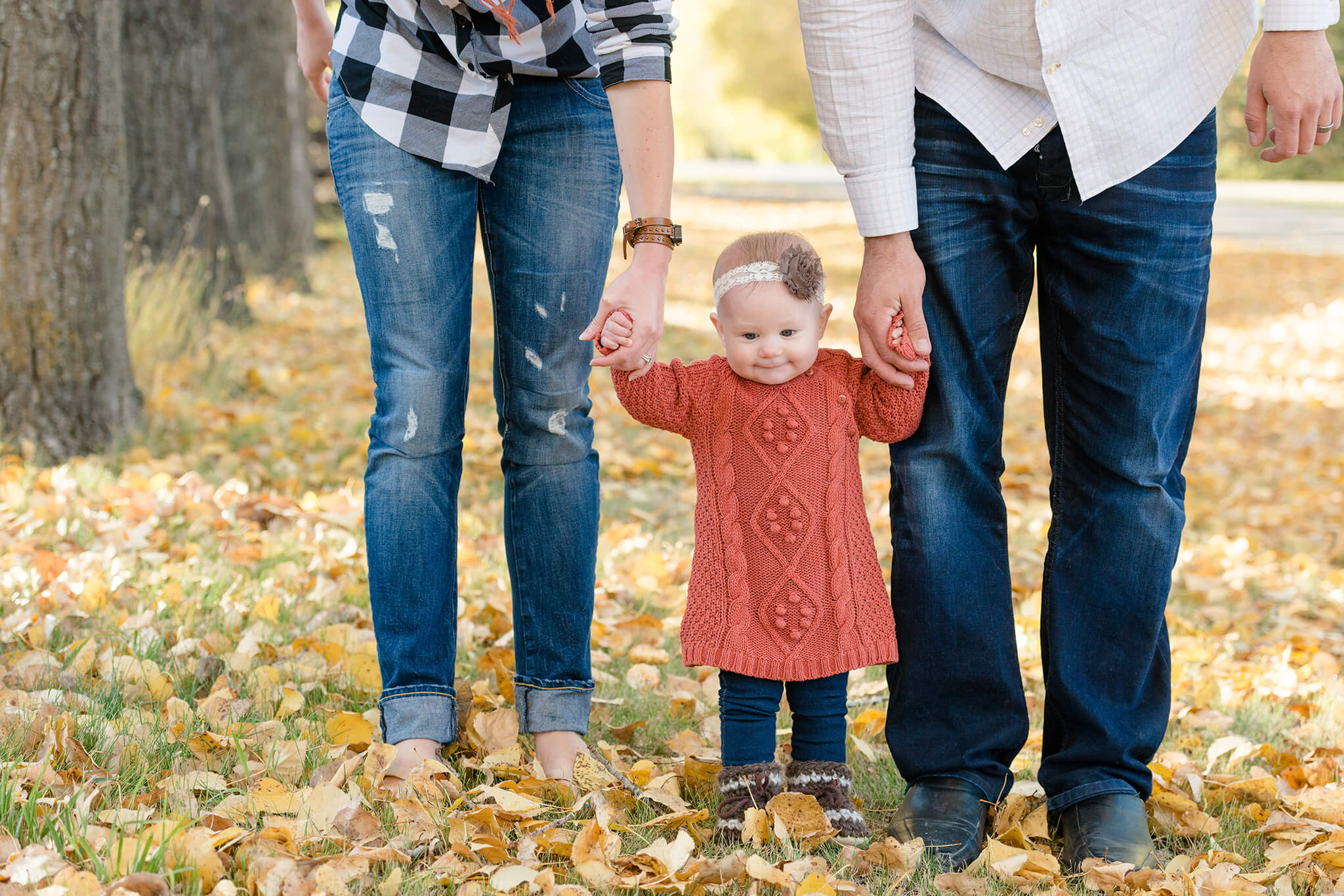 Little girl holding hands with her mom and dad in yellow leaves