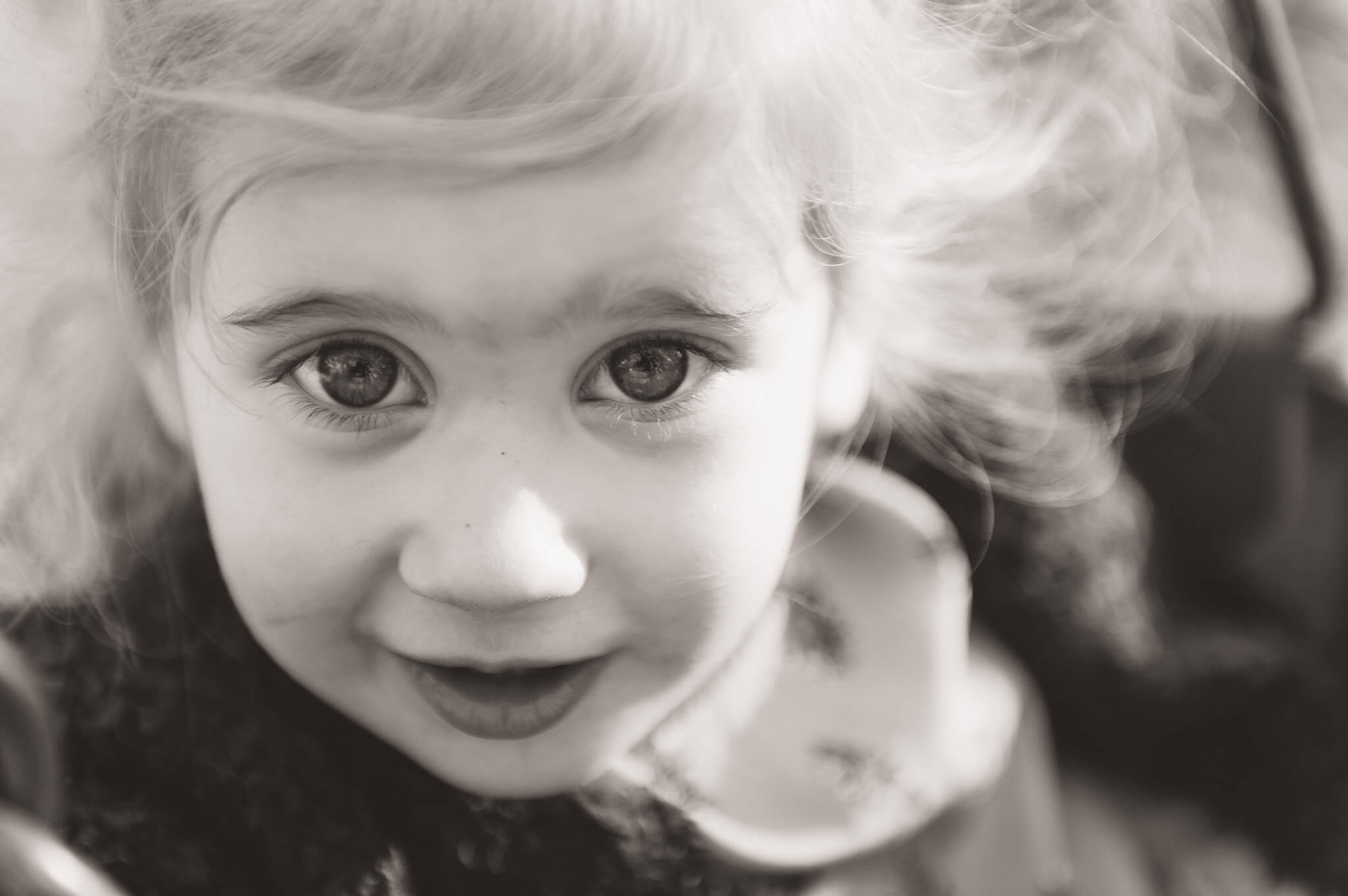 Little girl with big beautiful eyes playing on the swing