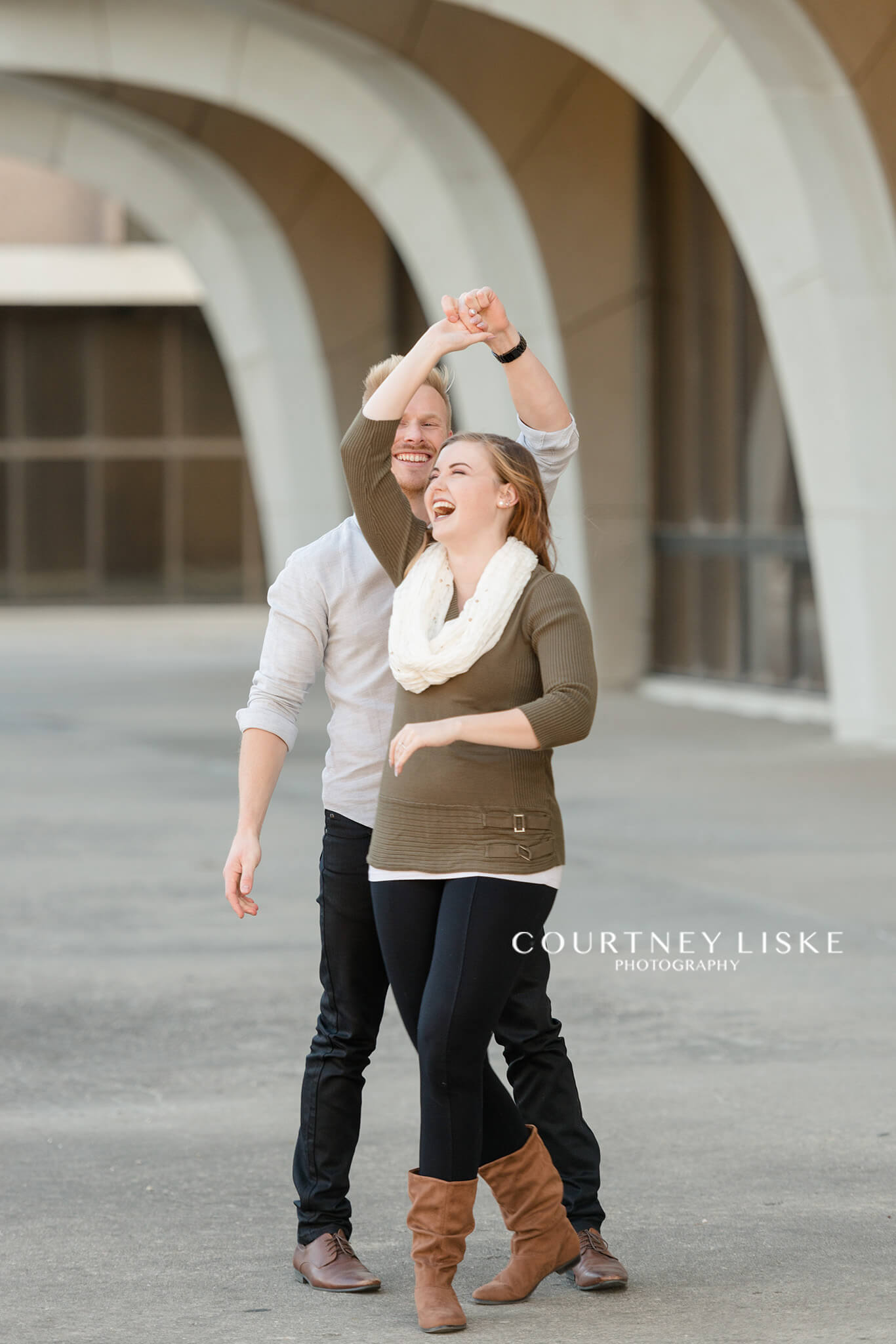 Man and woman dance together atop the University of Regina Library
