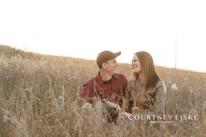 Man and woman sitting in tall grass at sunset