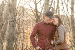 Man in baseball hat and woman in leather jacket amongst trees
