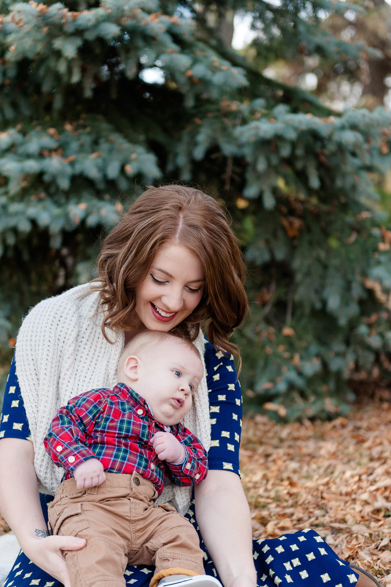 Mom cuddles with baby boy in the fallen leaves