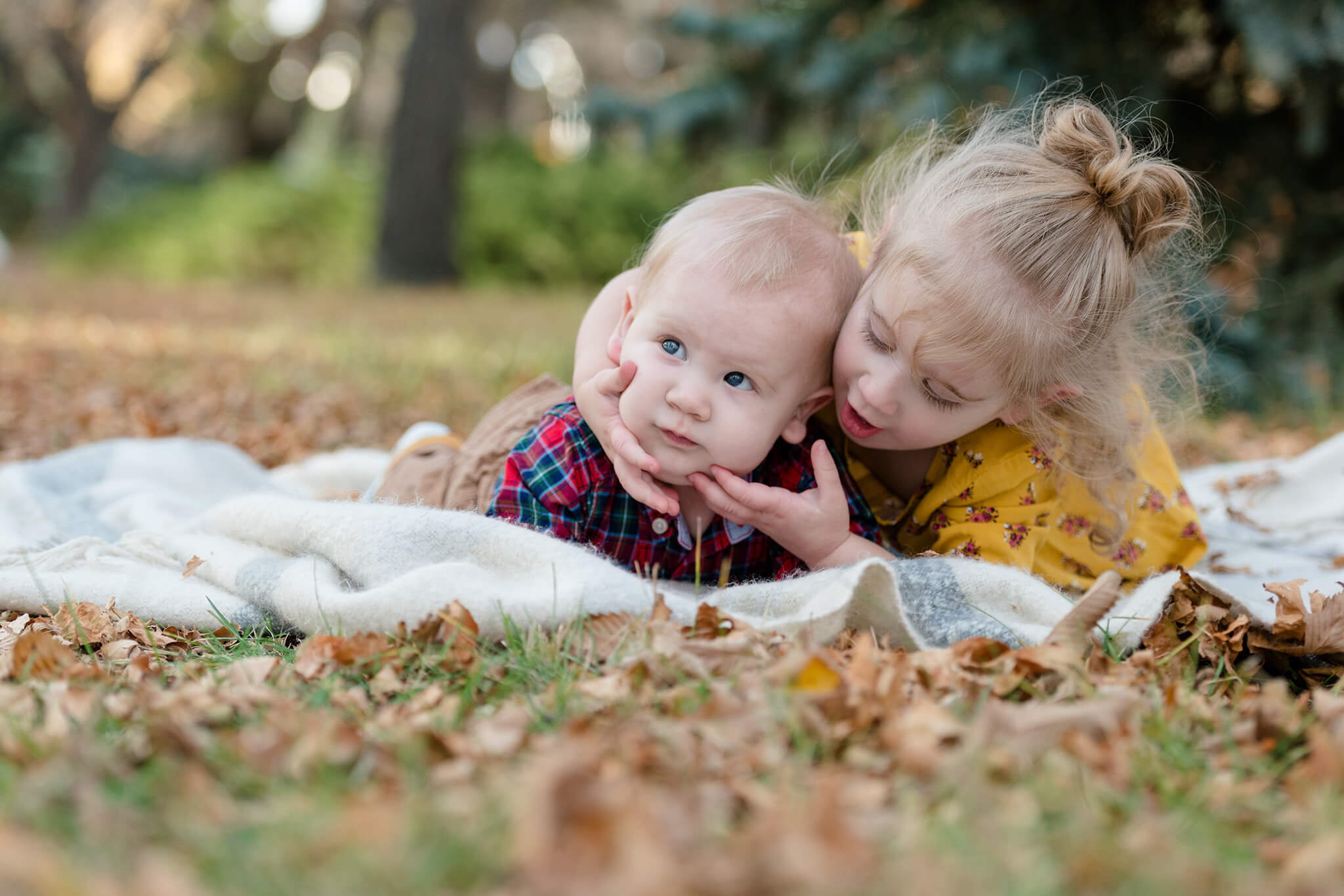 Older sister plays with baby brothers cheeks