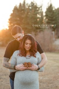 Couple hold brown baby shoes in hands