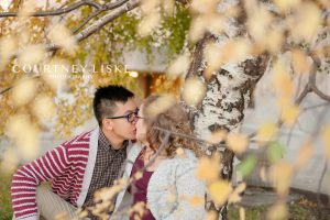 Couple kisses under a willow tree