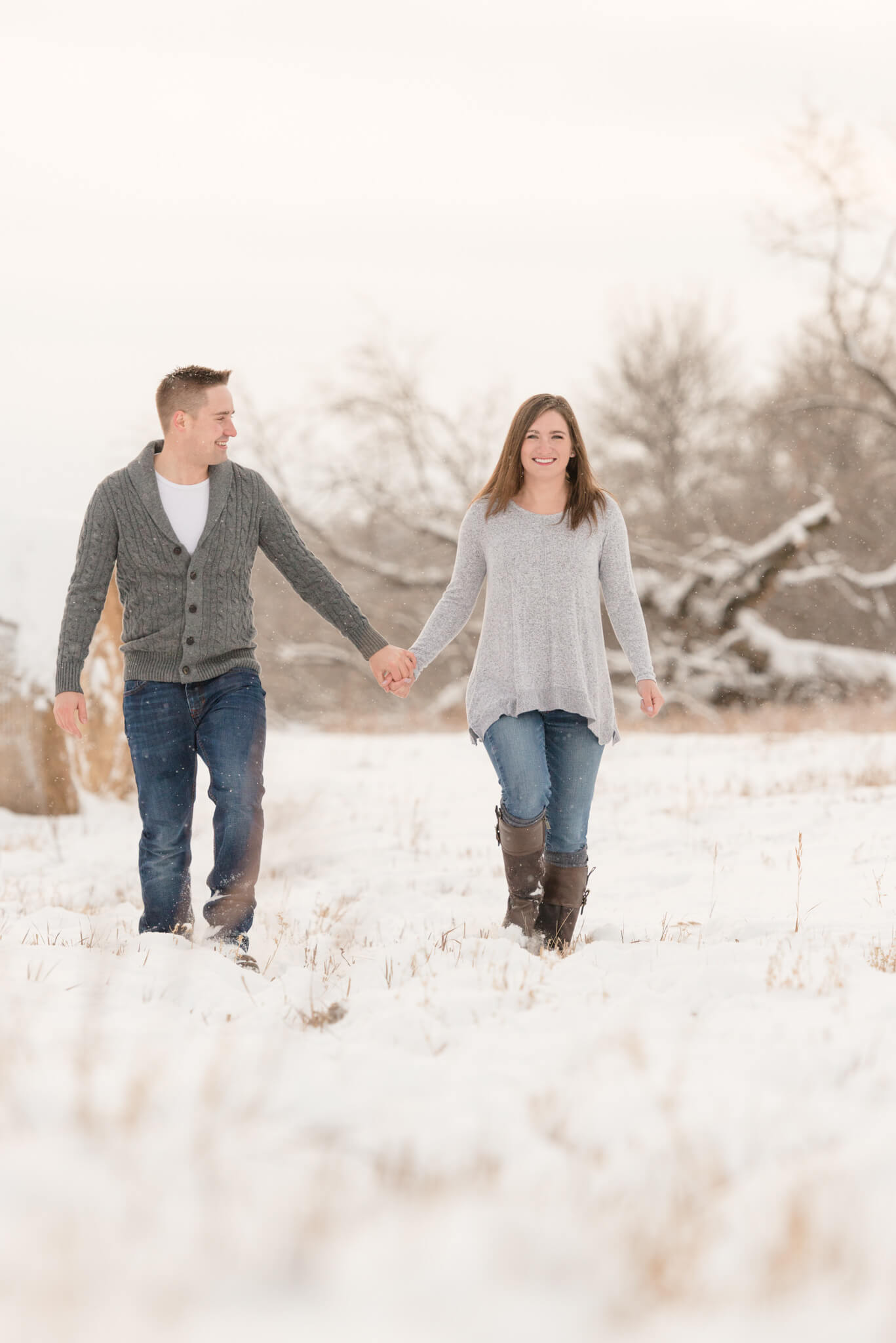 Couple walks hand in hand through the snow