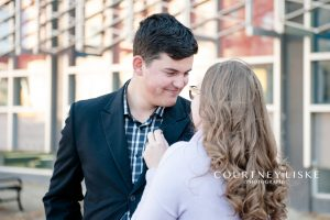 Man in black blazer and plaid shirt with fiance in purple