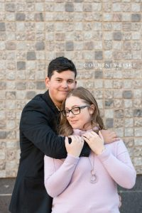 Man smiles at the camera as he holds fiance in lilac sweater