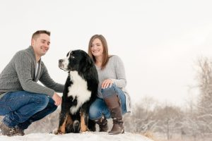 Mark & Kyra on top of a snow covered bale with their Bernese Mountain dog