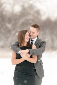 Woman in black dress and man in grey suit in the snow in Lumsden Valley