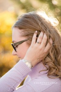 Woman in lilac sweater with glasses and engagement ring