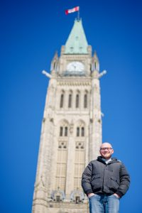 Man in winter jacket stands in front of the Peace Tower in Ottawa