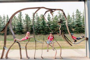 Three children sitting on elephant at Calgary Zoo