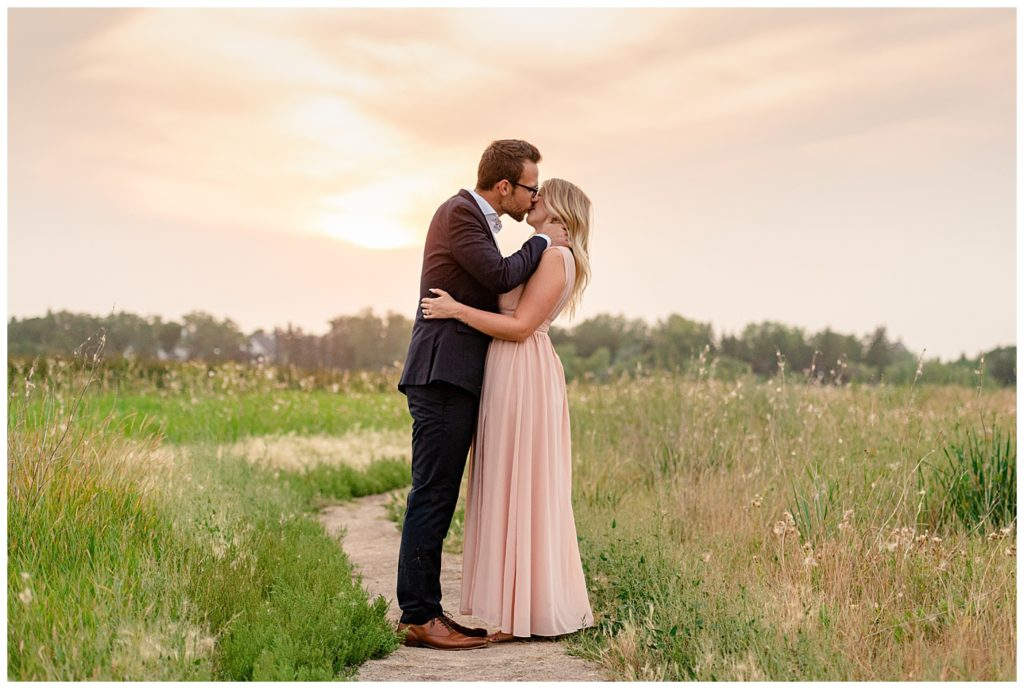 Regina Engagement Photography - Engagement Session - Couple kiss in a field of tall grass at sunset inside the Wascana Habitat Conservation Area - Blush chiffon dress - Black suit