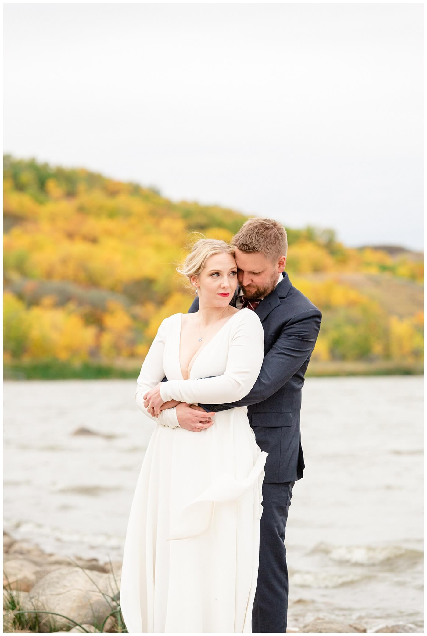 Regina Wedding Photographer - Tyrel - Allison - Bride looks out over the water as her Groom embraces her