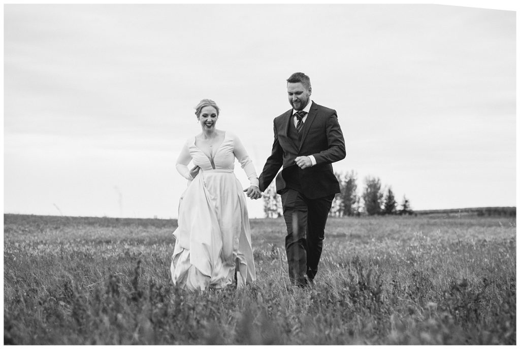 Regina Wedding Photography - Tyrel - Allison - Bride & Groom run through the field hand in hand