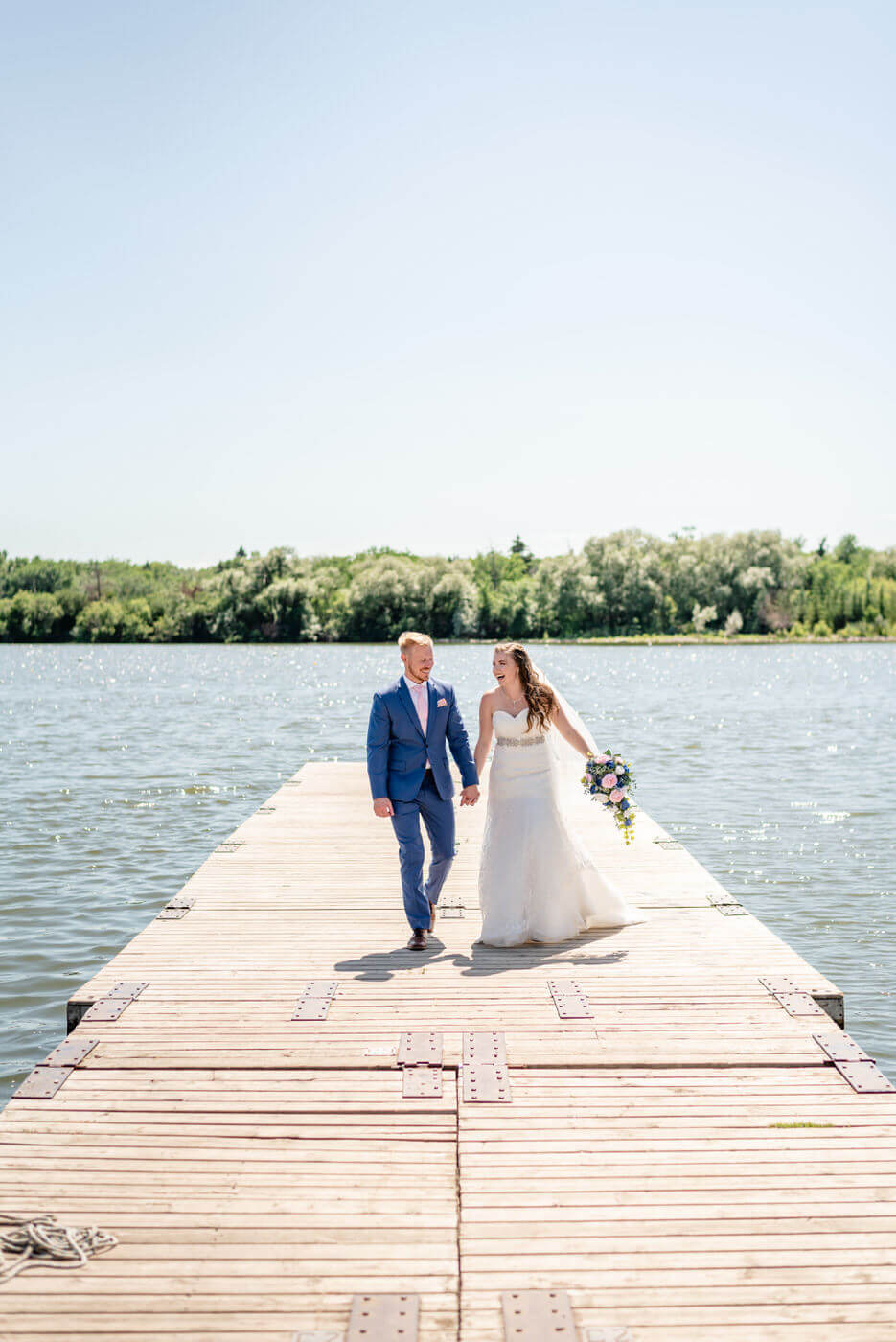 Evan & Chantel - Bride & Groom walking on dock on Wascana Lake in Regina