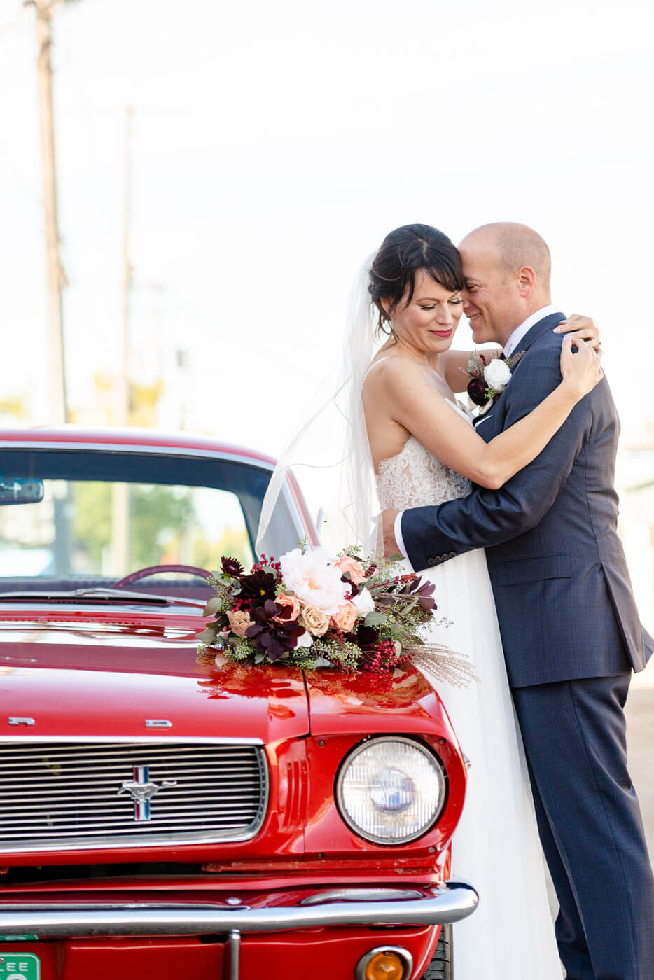 Scott & Keely - Bride & Groom leaning on vintage mustang at black and white wall in Regina