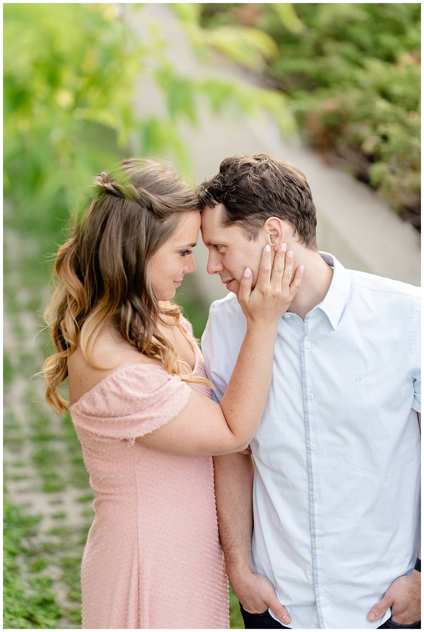 Regina Engagement Photographer - Adam - Sarah - Natural Light Engagement Session in Wascana Park - CBC Regina Building - Pulling in her future husband for a kiss