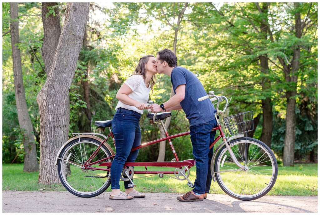 Regina Engagement Photographer - Adam - Sarah - Natural Light Engagement Session in Wascana Park - Couple riding tandem bicycle stop for a kiss