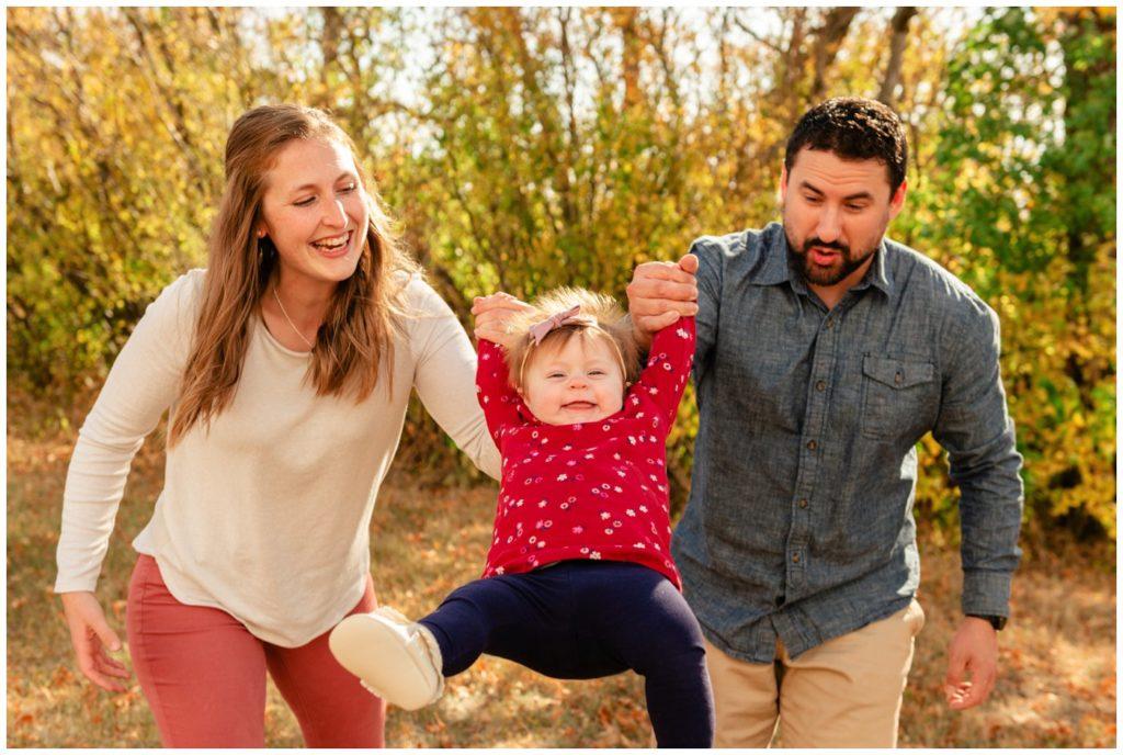 Regina-Family-Photography-Eyre-Family-Douglas-Park-Hill-06-Parents-swinging-child-