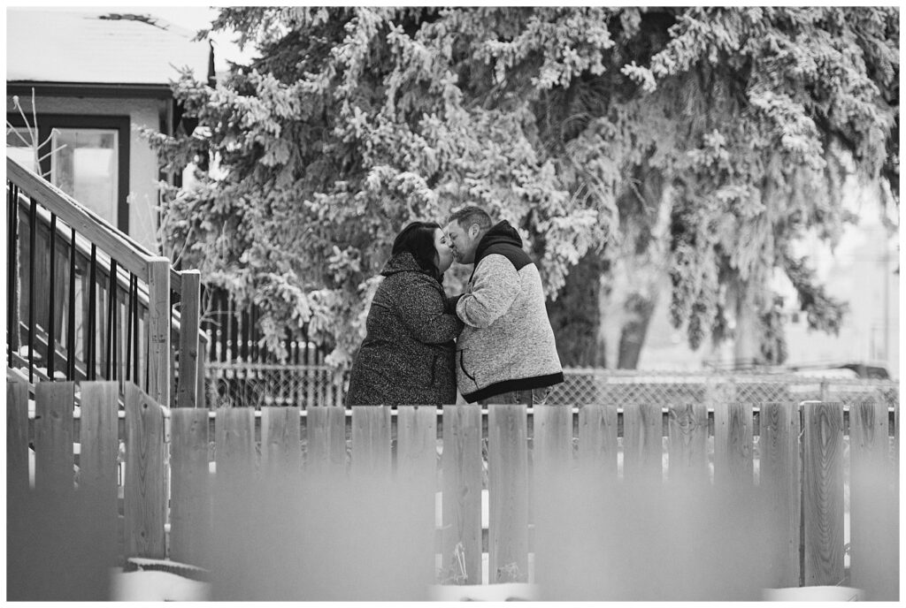 Regina Family Photography - Ashley - Scott - Couple share a kiss in the snow in their front yard