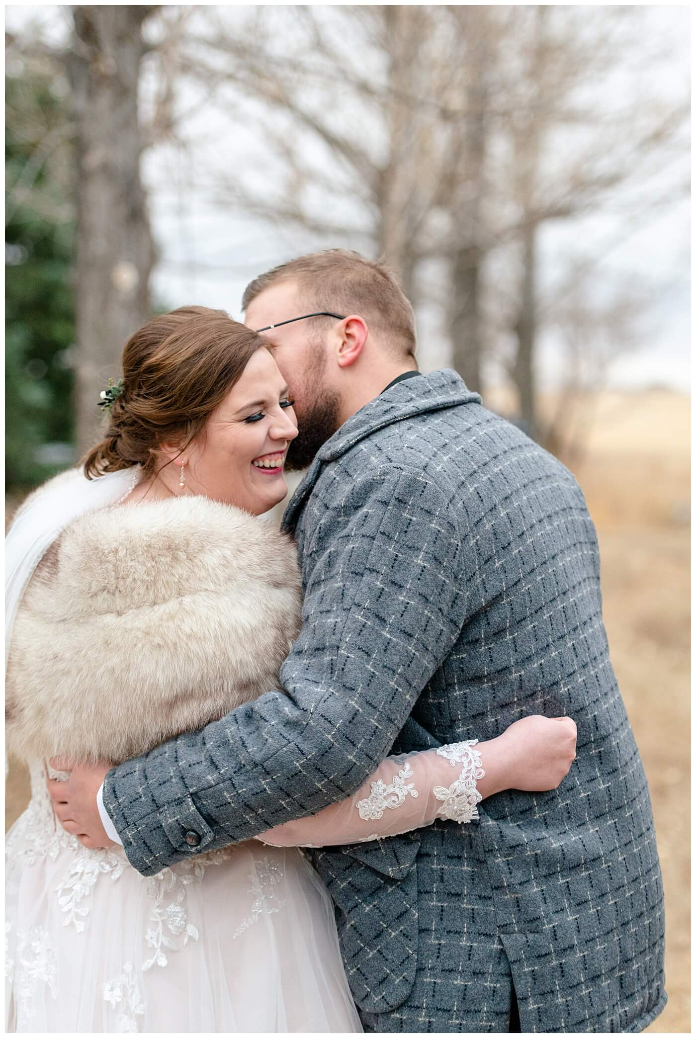 Regina Wedding Photographer - Kolton - Maxine - Groom whispers in the brides ear as he keeps her warm