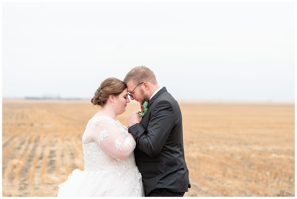 Regina Wedding Photographers - Kolton - Maxine - Bride & groom stand in a harvested wheat field