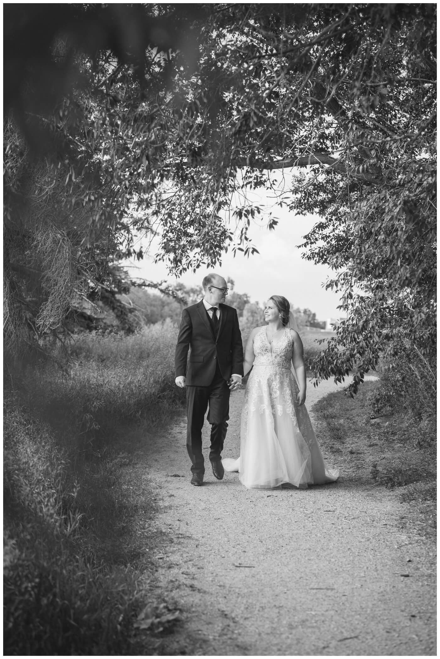 Colter & Jillyan - Encore Wedding Session - 04 - Bride & Groom walking on a path in black and white