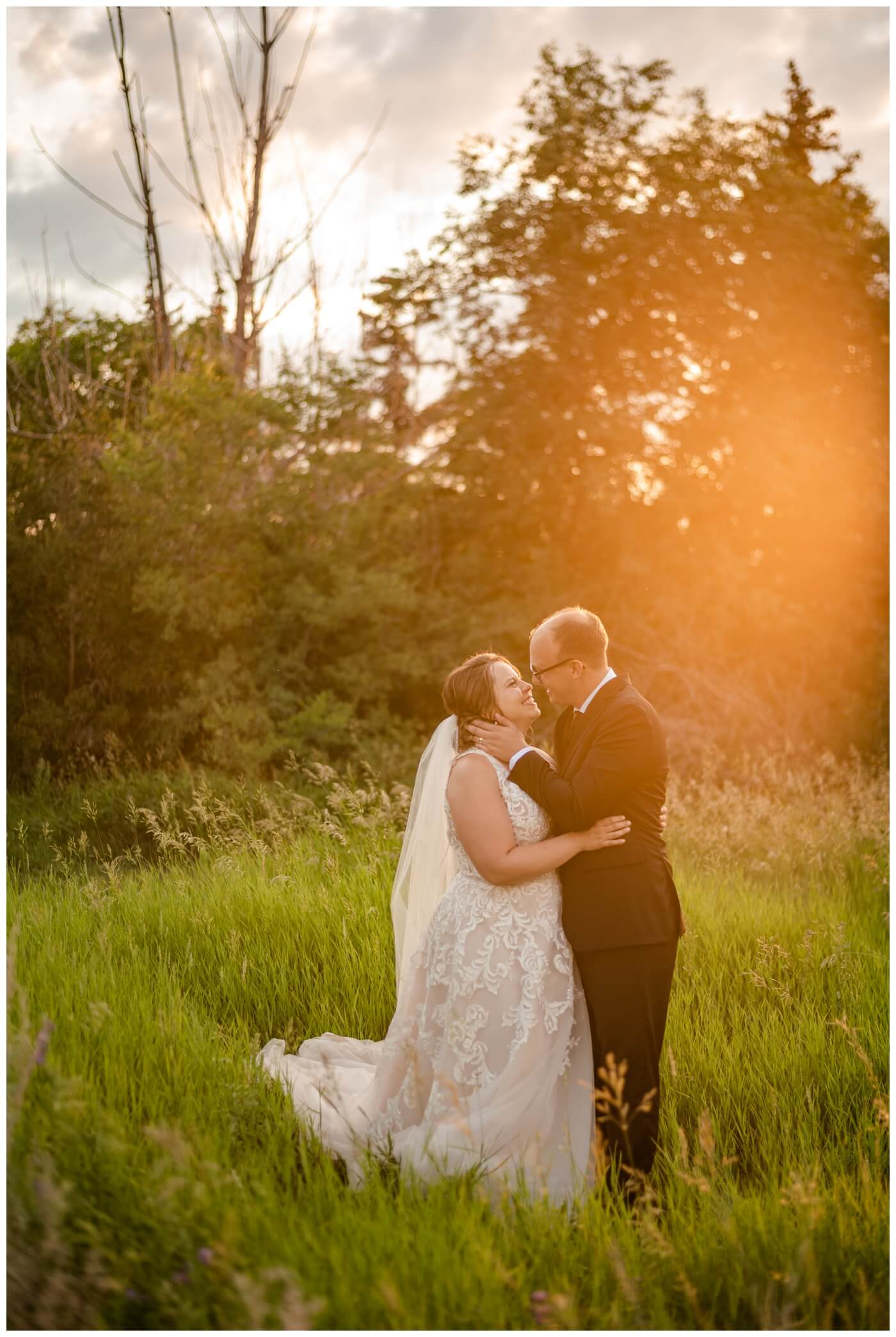 Colter & Jillyan - Encore Wedding Session - 09 - Bride & Groom kissing in field with sunflare at AE Wilson Park in Regina