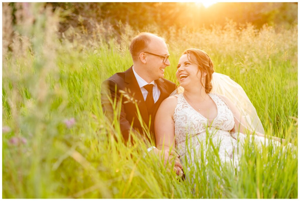 Colter & Jillyan - Encore Wedding Session - 10 - Bride and groom sitting in field with sunflare