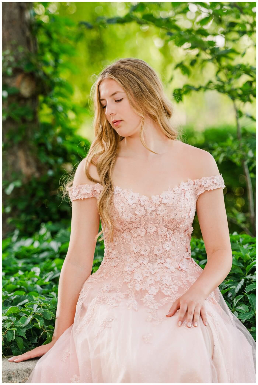 Rachel Vanderhooft Graduation -Graduate sits amongst greenery in her blush dress from NWL Regina