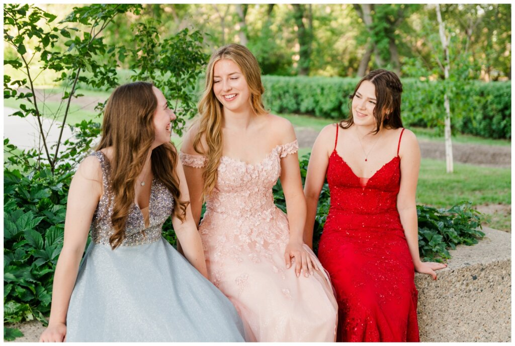Graduate girls sit together on stone wall