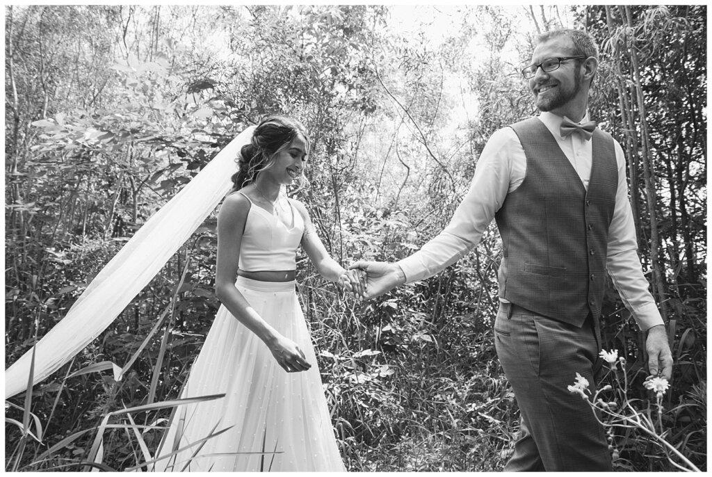 Stephen & Sarah Wedding - 11 - Groom leading bride through forest area at Wascana Park
