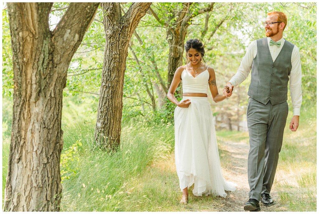 Stephen & Sarah Wedding - 14 - Bride & Groom strolling near the Saskatchewan Science Centre