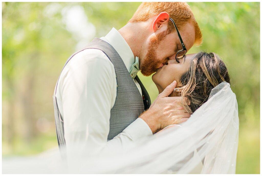 Stephen & Sarah Wedding - 16 - Bride & Groom kissing with veil swooping