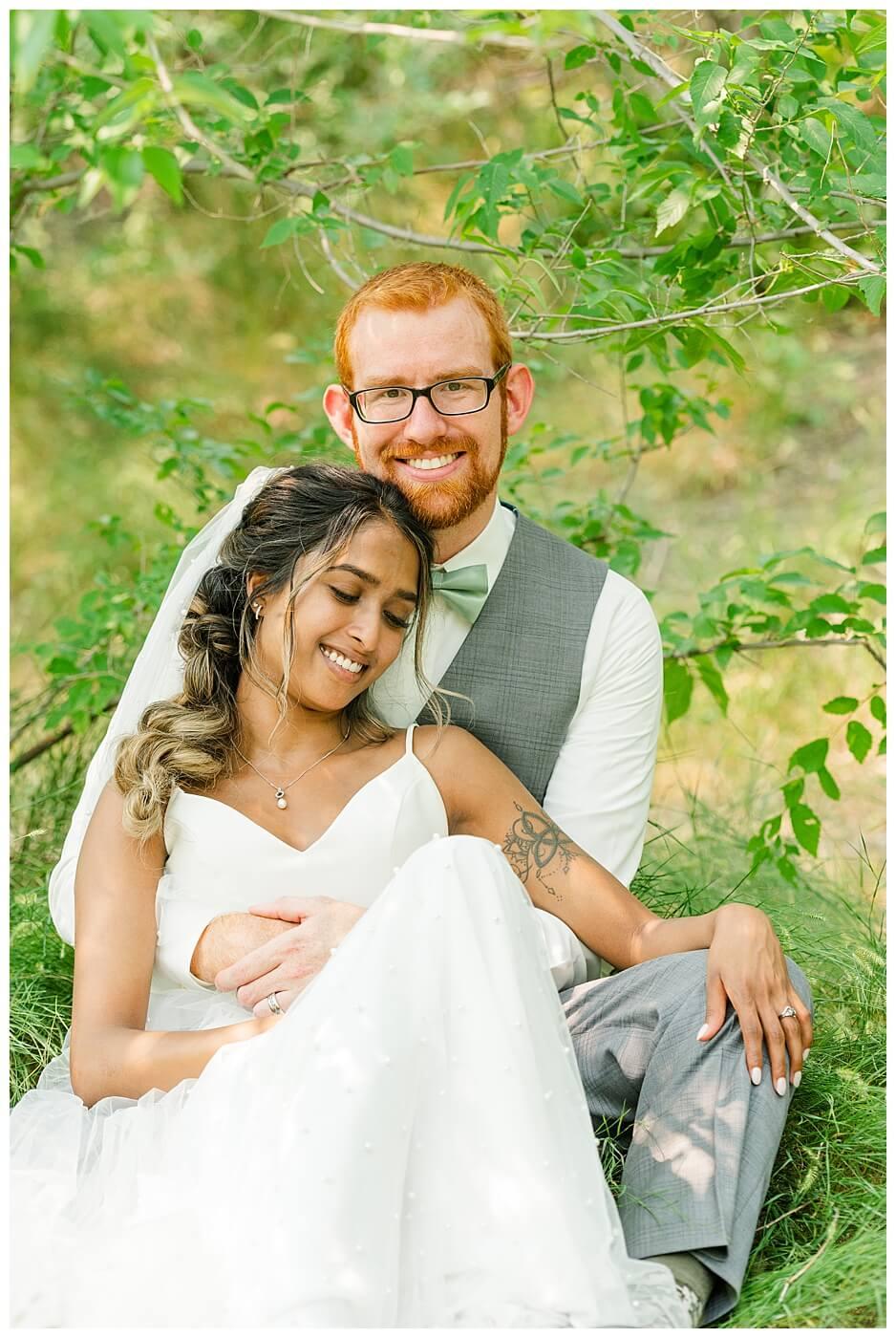 Stephen & Sarah Wedding - 17 - Bride and groom sitting with groom looking at camera