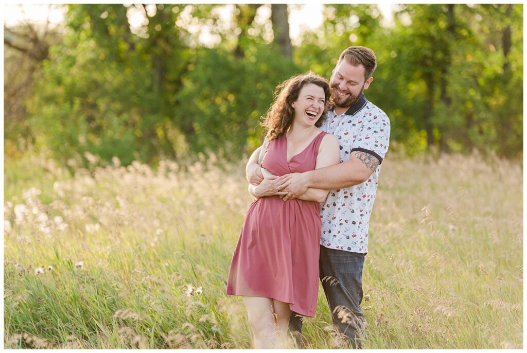 Mitch & Val - Engagement Session in Wascana Habitat Conservation Area - 04 - Couple snuggling and laughing in a field