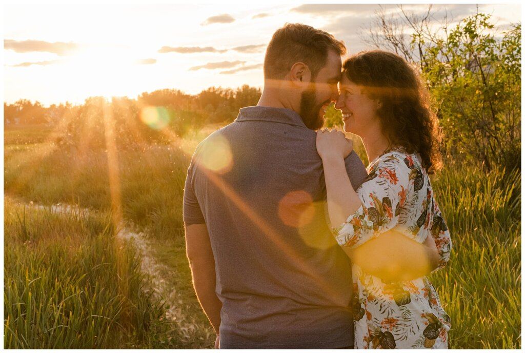 Mitch & Val - Engagement Session in Wascana Habitat Conservation Area - 09 - Couple with sunflare at sunset