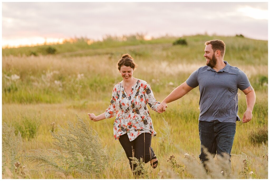 Mitch & Val - Engagement Session in Wascana Habitat Conservation Area - 11 - Couple frolicking in a field