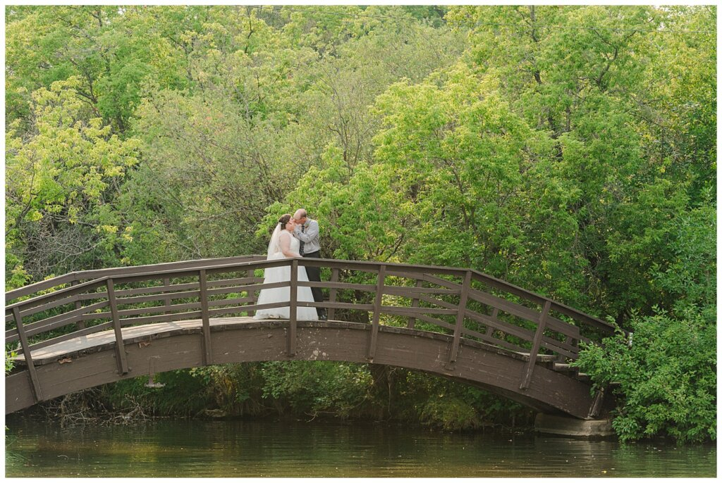 Sheldon & Amy - Besant Campground Wedding - 20 - Couple share a kiss on the bridge