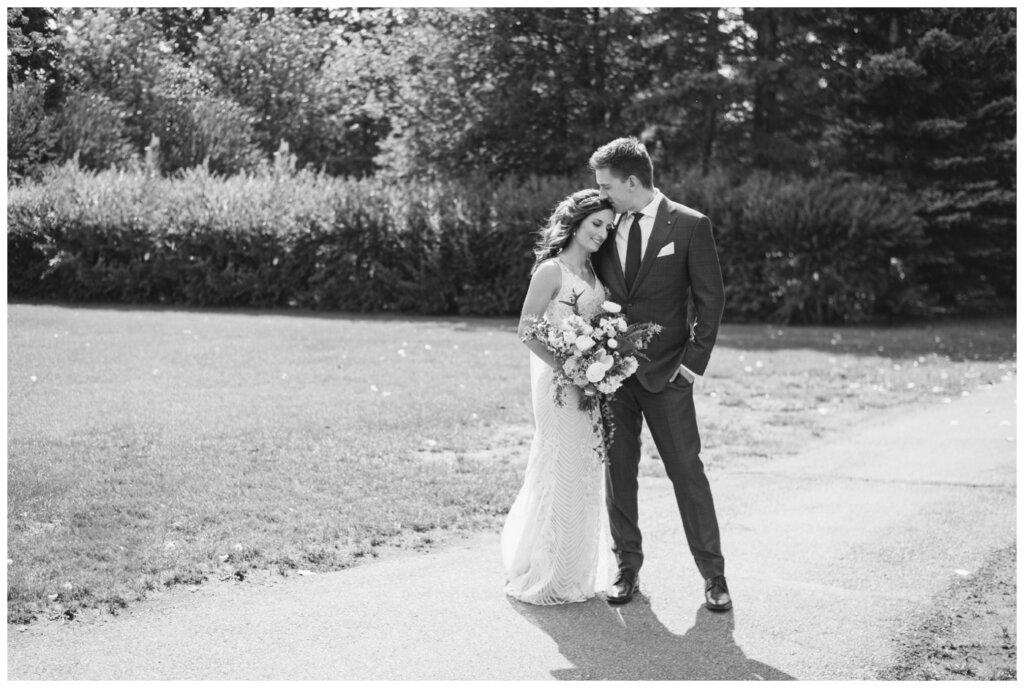 Taylor & Jolene - Emerald Park Wedding - 10 - Bride & Groom on walking path in White City