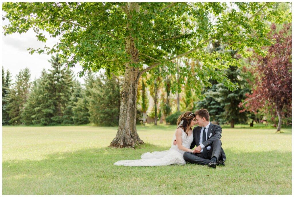 Taylor & Jolene - Emerald Park Wedding - 13 - Bride & Groom sit quietly in the park